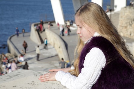 Thoughtful girl child standing on the waterfront looking down Stock Photo