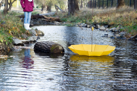 Bright yellow umbrella swims on the river in the wind in autumn