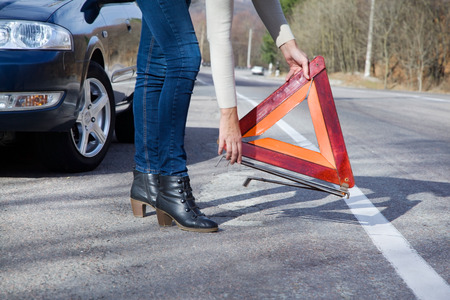 Car on the roadside a woman holding a warning triangle
