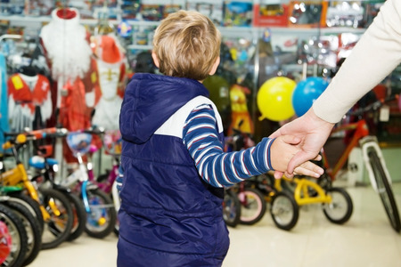 Moeder stevig vast te houden van de baby bij de hand in een speelgoedwinkel