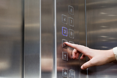 lift hands: Female finger presses the button on the glowing panel elevator