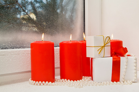 window sill: Christmas gifts in a composition with candles and beads on a snow-covered window sill Stock Photo