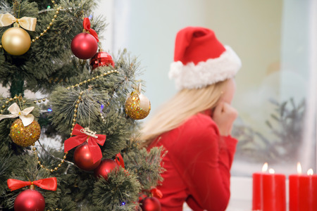 Christmas tree girl in santa hat near the window in the background blurring