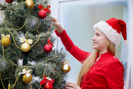 decorates: Girl in santa hat decorates a Christmas tree with a smile on his face