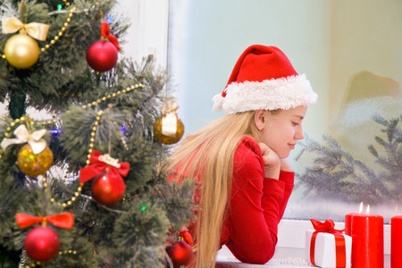 Beautiful girl near the window waiting for Christmas looking at a candle flame