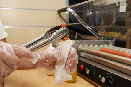 Salesman professional making a hot dog in a fast-food Stock Photo