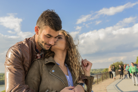 Attractive woman kissing her boyfriend under the bright blue sky