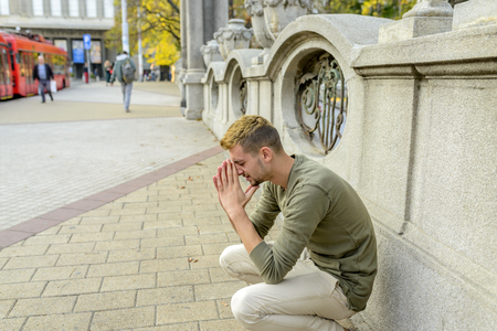 Stressed man is praying to the God and hoping for better times to come Imagens