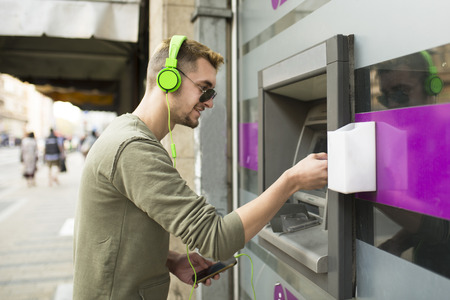 Young handsome man with sunglasses and headphones taking money from the ATM Stock Photo