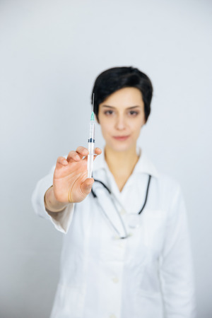 Female doctor with syringe, isolated on white background. Medicine and health care concept.
