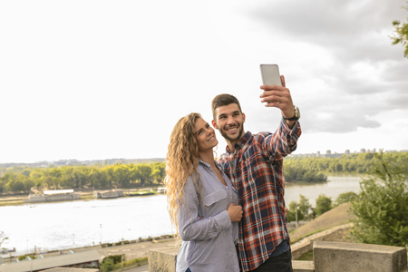 Happy lovers in moments of happiness taking a selfie photos and enjoying the time in nature Banco de Imagens