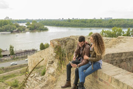 Attractive long haired woman and her boyfriend sitting on the wall and using their smart phone