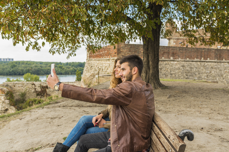 Young man is taking selfie with his beautiful girlfriend while sitting on the bench in the park under the tree