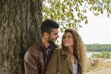 Happy and attractive couple with love emotions standing under the tree