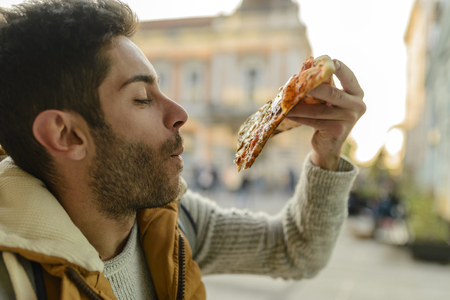 Handsome bearded young man with orange jacket eating pizza in the city street
