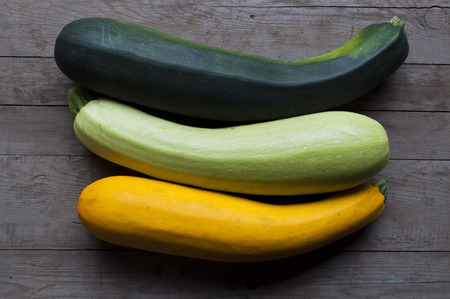 courgettes: Three marrow (courgettes, kabachek) on a wooden plank Stock Photo