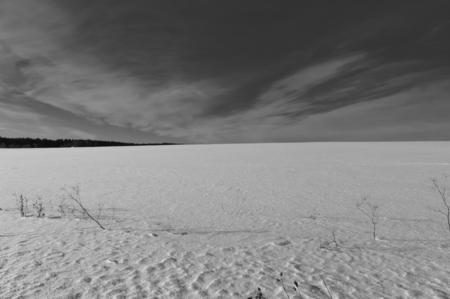snowy field: Snowy field and dark sky, black and white photo Stock Photo