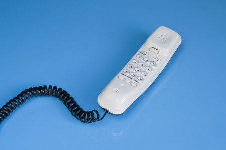 handset: White handset on blue glossy background Stock Photo