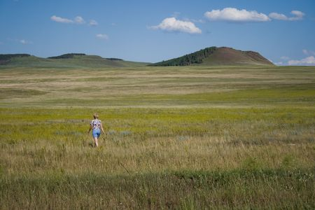 single woman: Single woman going forward in steppe. Hills on horizont Stock Photo