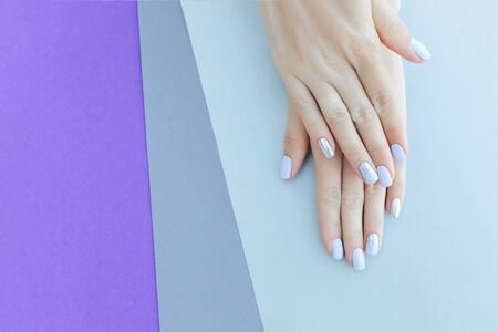 Gorgeous manicure, purple tender color nail polish, closeup photo. Female hands over simple background of casual clothes.