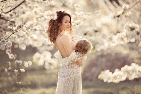Joven madre amamanta a su hija en un parque de cerezos en flor. Están vestidos con vestidos blancos. Atardecer.