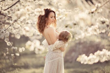 Young mother breastfeeds her daughter in a flowering cherry park. They are dressed in white dresses. Sunset.