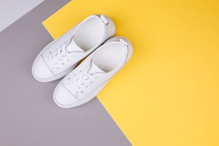 Fashion, sport, blog, blogging, lifestyle, well-being trendy concept. Pair of white female sneakers on yellow and grey background, top view, copy space, flat lay.