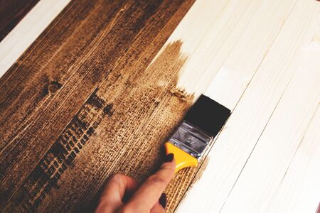 Man paints a wooden surface with dark paint.
