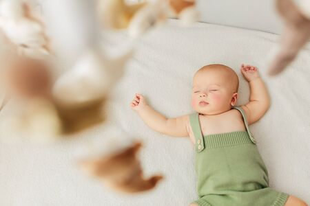 Little baby girl sleeps on a bed in a green suit, playmobile revolves over her.