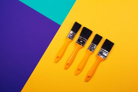 Brush with yellow handle on blue yellow purple background. Main trend concept. Trend colors.