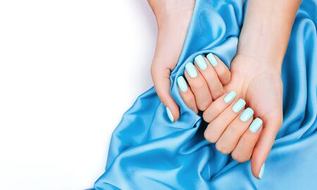 Hands of a young girl on a Blue silk cloth, manicure on a background , green polish.