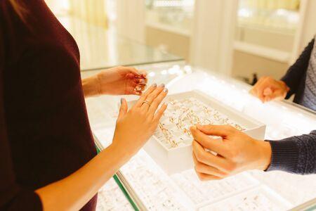 Boutique de bijouterie à l'intérieur - petite entreprise. Vente d'or et de diamants. mains féminines et masculines. le vendeur montre des bijoux et une chaîne