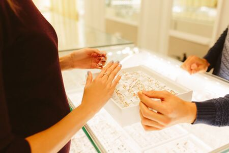 Jewelry store shop indoors - small business. Gold and diamonds for sale. female and male hands. seller shows jewelry and chain