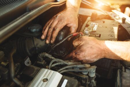 Close-up of mechanic repairing a car without gloves. Banque d'images