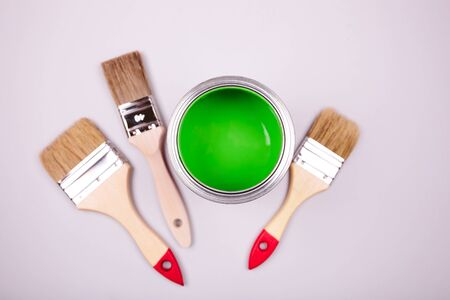 Brush with white handle on open can of green paint on grey pastel background. Main trend concept.