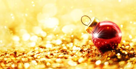 Christmas ball on abstract gold blur background.