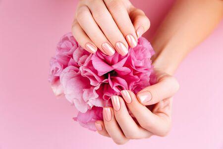 신선한 eustoma와 아름 다운 여자 손입니다. 스파 및 매니큐어 개념입니다. 핑크 매니큐어와 여성 손입니다. 부드러운 피부, 스킨케어 개념. 뷰티 네일. 베이지색 배경 위에 스톡 콘텐츠