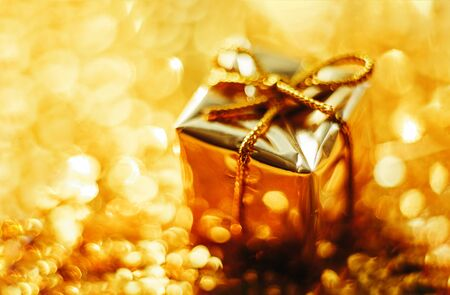 Golden gift on defocused lights background close up. Archivio Fotografico - 134675308
