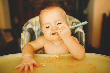 beautiful blond boy eats porridge and laughs Stock Photo