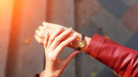 street style fashion details. close up, young fashion blogger wearing a jacket and a analog wrist watch. stylish woman checking the time on her watch. autumn fall season.