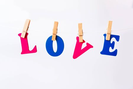 Clothes pegs and I LOVE YOU words on papers on rope on white background Valentines day concept