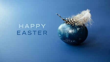 Easter egg wirh feather on blue background with empty space . Easter card.