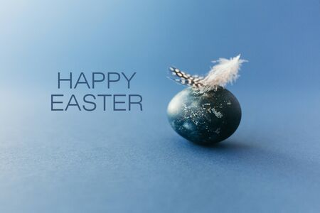 Easter egg wirh feather on blue background with empty space . Easter card. Classic blue color of year 2020 스톡 콘텐츠