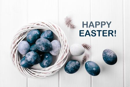 Group of light blue eggs in their nest on a white wooden background. Happy Easter decoration. Classic blue color of year 2020