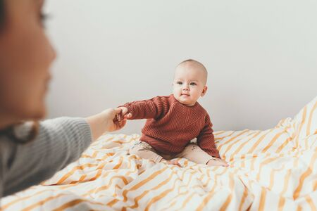 Beautiful little baby girl on the bed in a cozy brown sweater smiles. Concept of motherhood and childhood. Adorable six month old baby girl lying on the bad and looking into the camera. Mother hold li