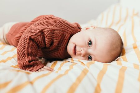 Beautiful little baby girl on the bed in a cozy brown sweater smiles. Concept of motherhood and childhood. Adorable six month old baby girl lying on the bad and looking into the camera.