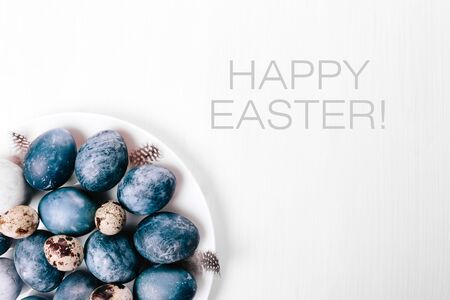 Beautiful group ombre blue Easter eggs with quail eggs and feathers on a white wooden background. Easter concept. Border eggs. Copy space for text. Classic blue color of year 2020