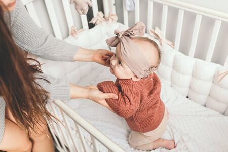 Beautiful baby girl in bed with her mom, light stylish interior. trying to stand. Concept of matherhood.