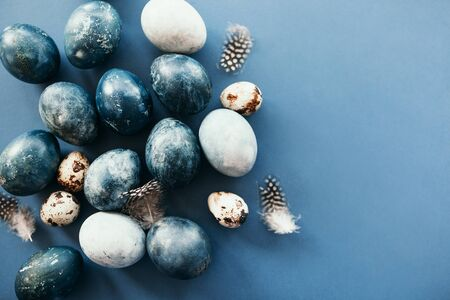 Beautiful group ombre blue Easter eggs with quail eggs and feathers on a blue background. Easter concept. Border eggs.