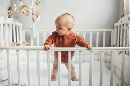 Beautiful little girl in a crib in a cozy light room in a sweater of fashionable shades. learns to stand at the support. cheerful little girl standing in the crib at home